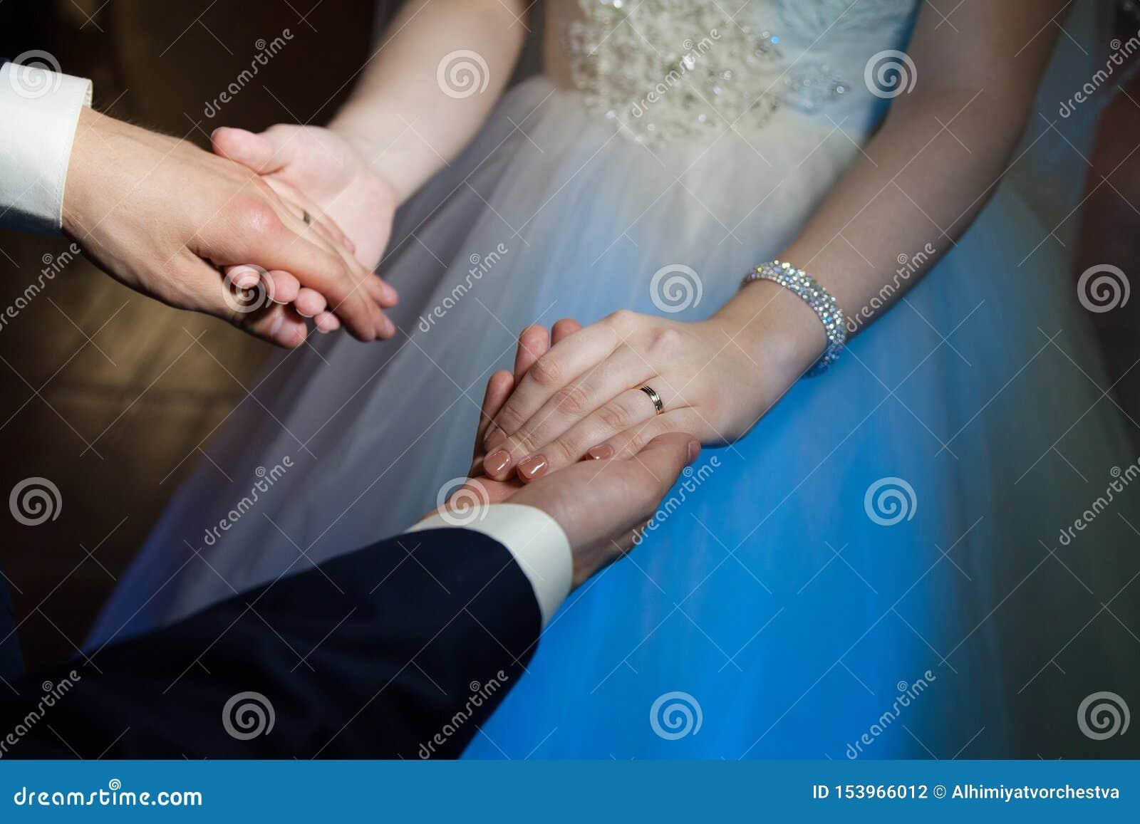 Bruid en bruidegomgreephanden tijdens de eerste dans, trouwringen