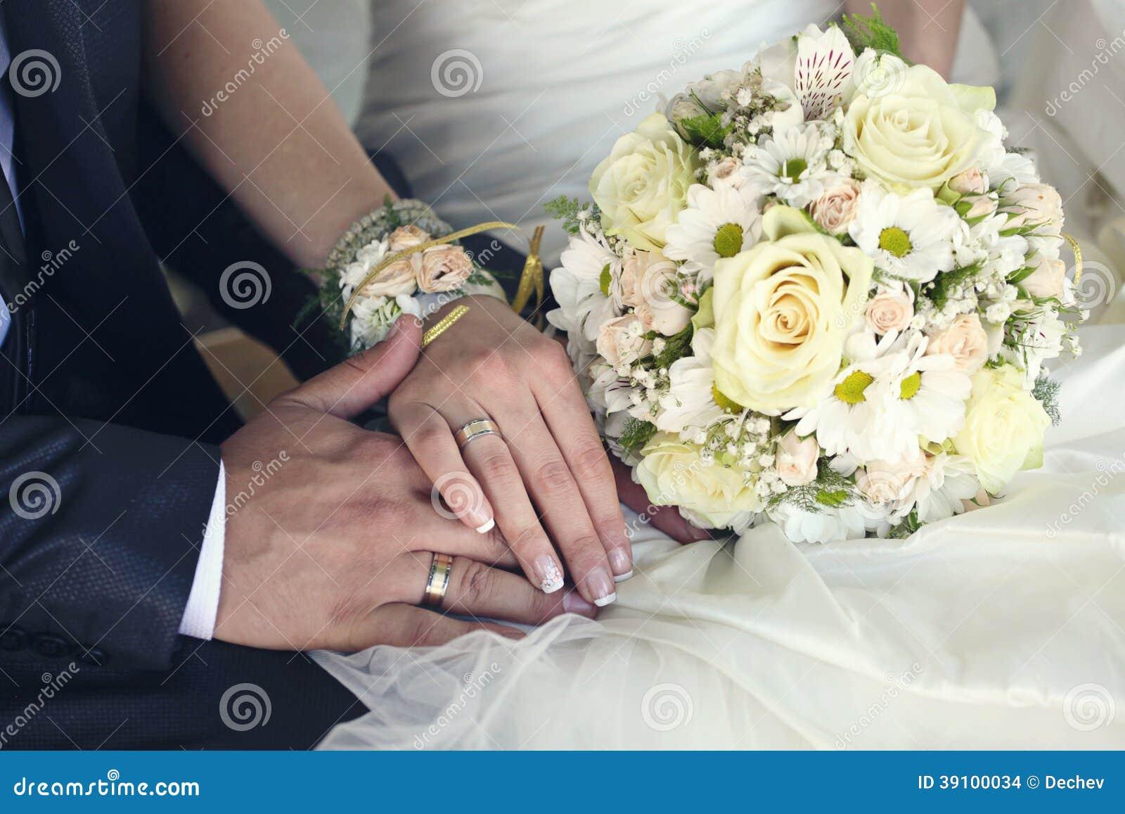 Bruid en van de bruidegom handen met trouwringen