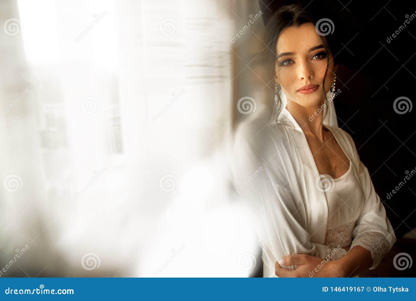 Bruid in mooie kledingszitting op stoel binnen in wit studiobinnenland als thuis Het in schot van de huwelijksstijl