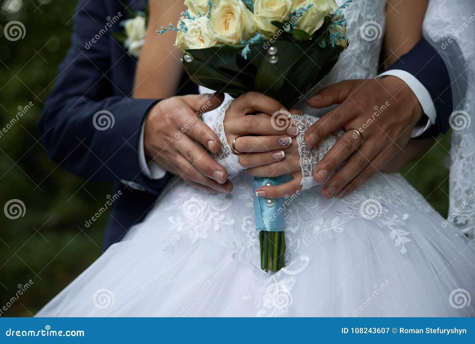 Bruidegom die bruid in witte kleding van achter boeketclose-up koesteren