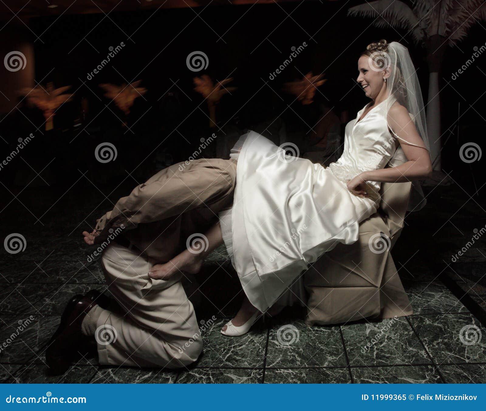 Bruidegom die de kouseband verwijdert