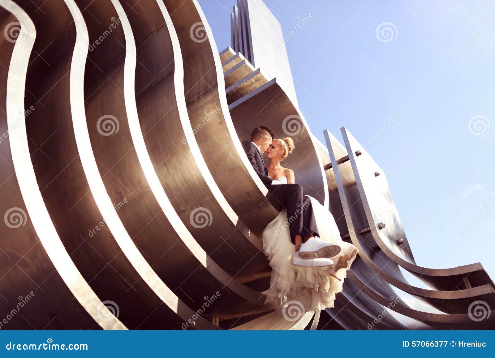 Bruidegom en bruid op een grote metaalbouw