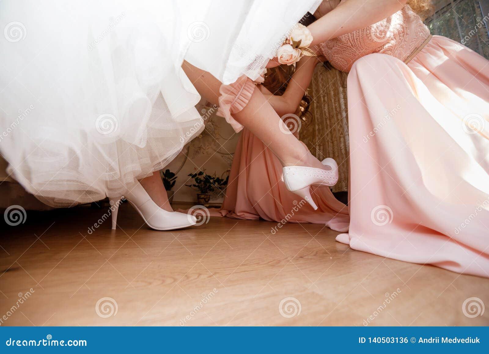 Bruidsmeisje die bruid voorbereiden op huwelijksdag het Bruidsmeisje helpt haar om vulling-juwelen op haar been te dragen