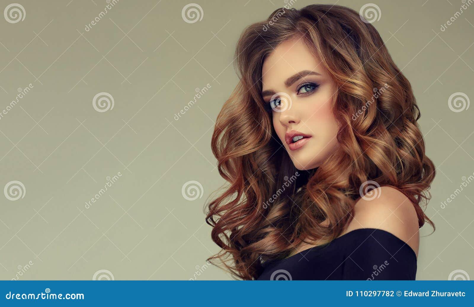 Bruine haired vrouw met omvangrijk, glanzend en krullend kapsel Kroeshaar