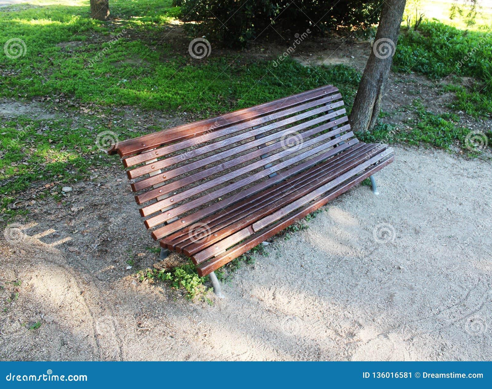Bruine houten bank met zetels aan één kant in het park
