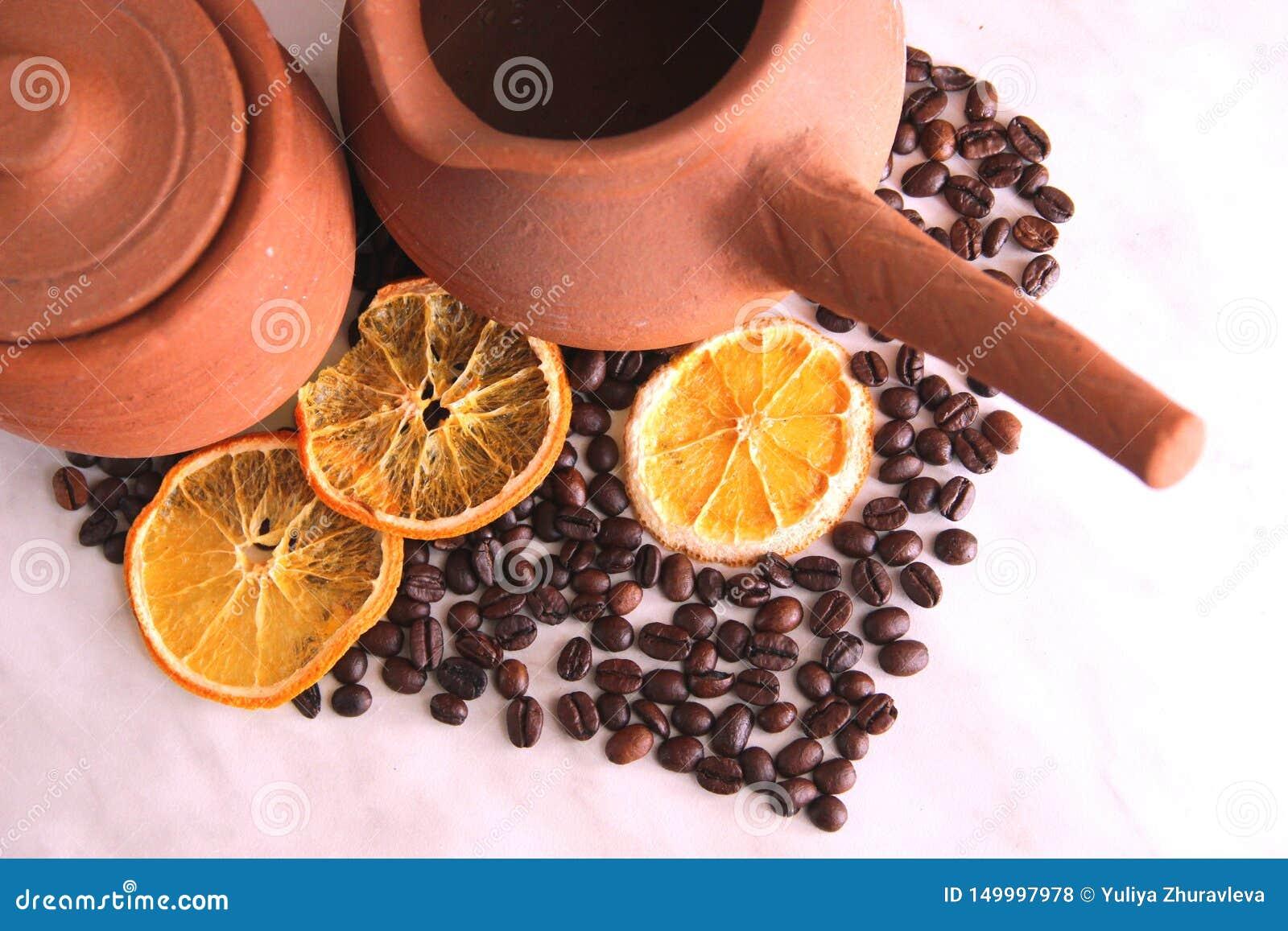 Bruine kleischotels, kruik met handvat voor koffie en kruikmelk, heel wat geroosterde koffiebonen en droge sinaasappelen, hart