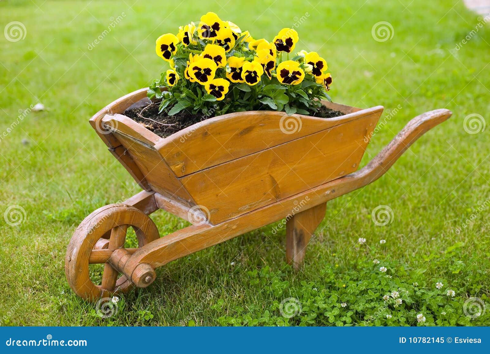 Bruine kruiwagen met gele bloemen