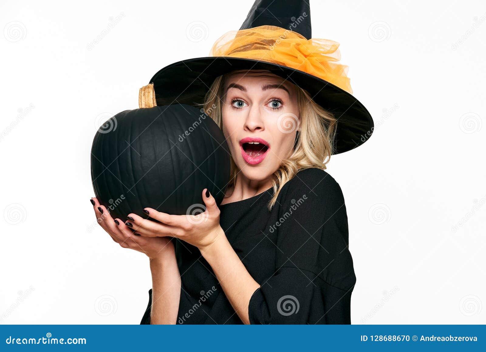 b490b30f24607 Bruja de Halloween con la expresión chocada que sostiene la calabaza negra  grande Mujer joven hermosa en las brujas sombrero y traje que sostienen la  ...