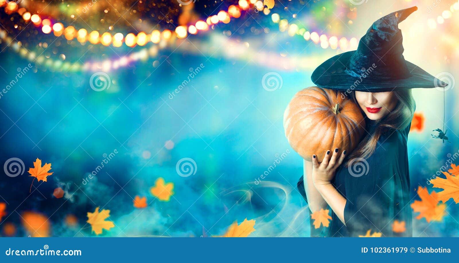 Bruja de Halloween con una calabaza tallada y las luces de la magia