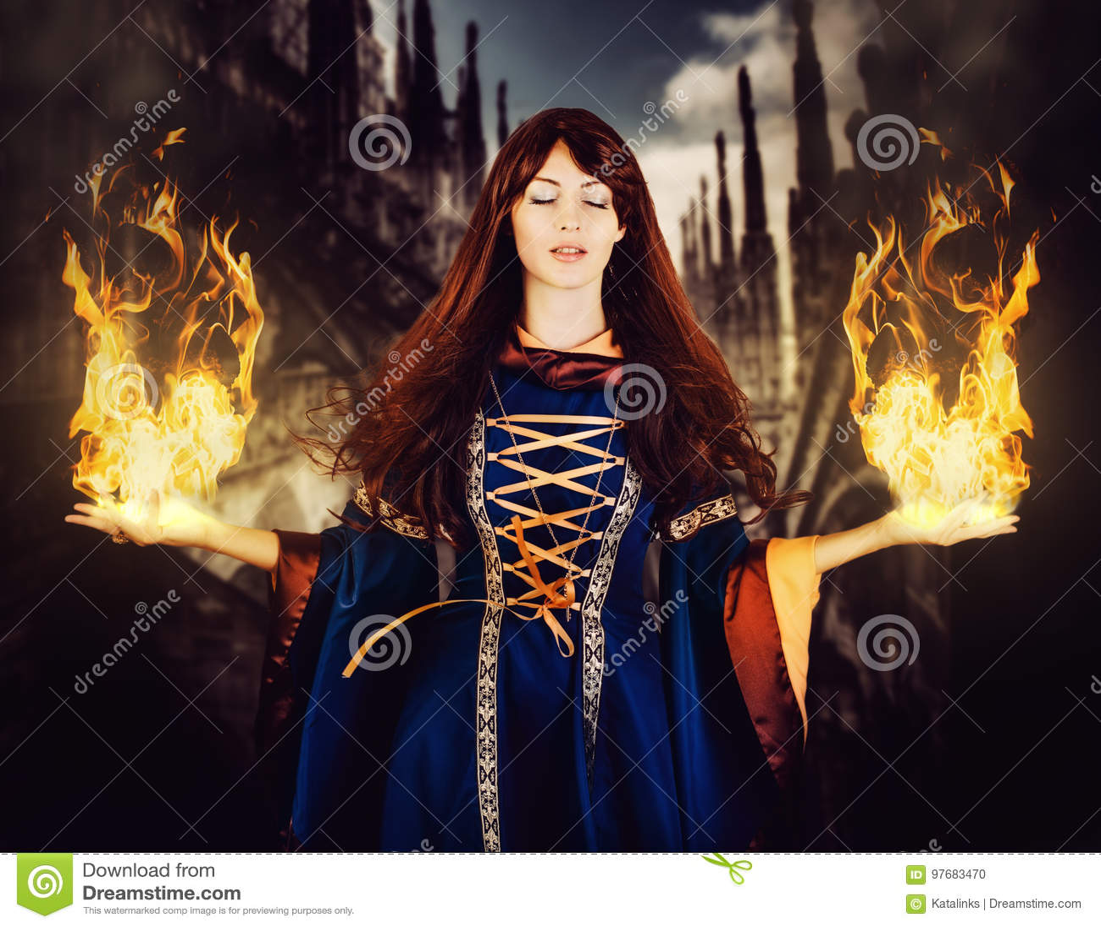 Bruja hermosa de la mujer en vestido medieval de la fantasía Fire Magic