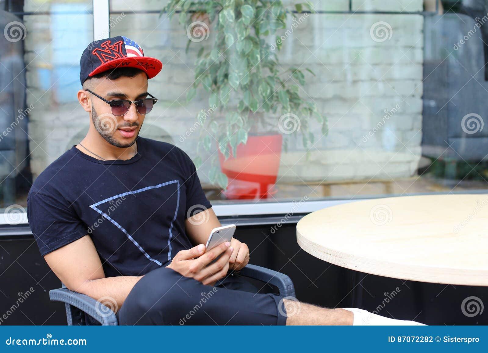 Bruk för en ringer sitter sitter ungt stiligt arabiskt grabb, att prata och