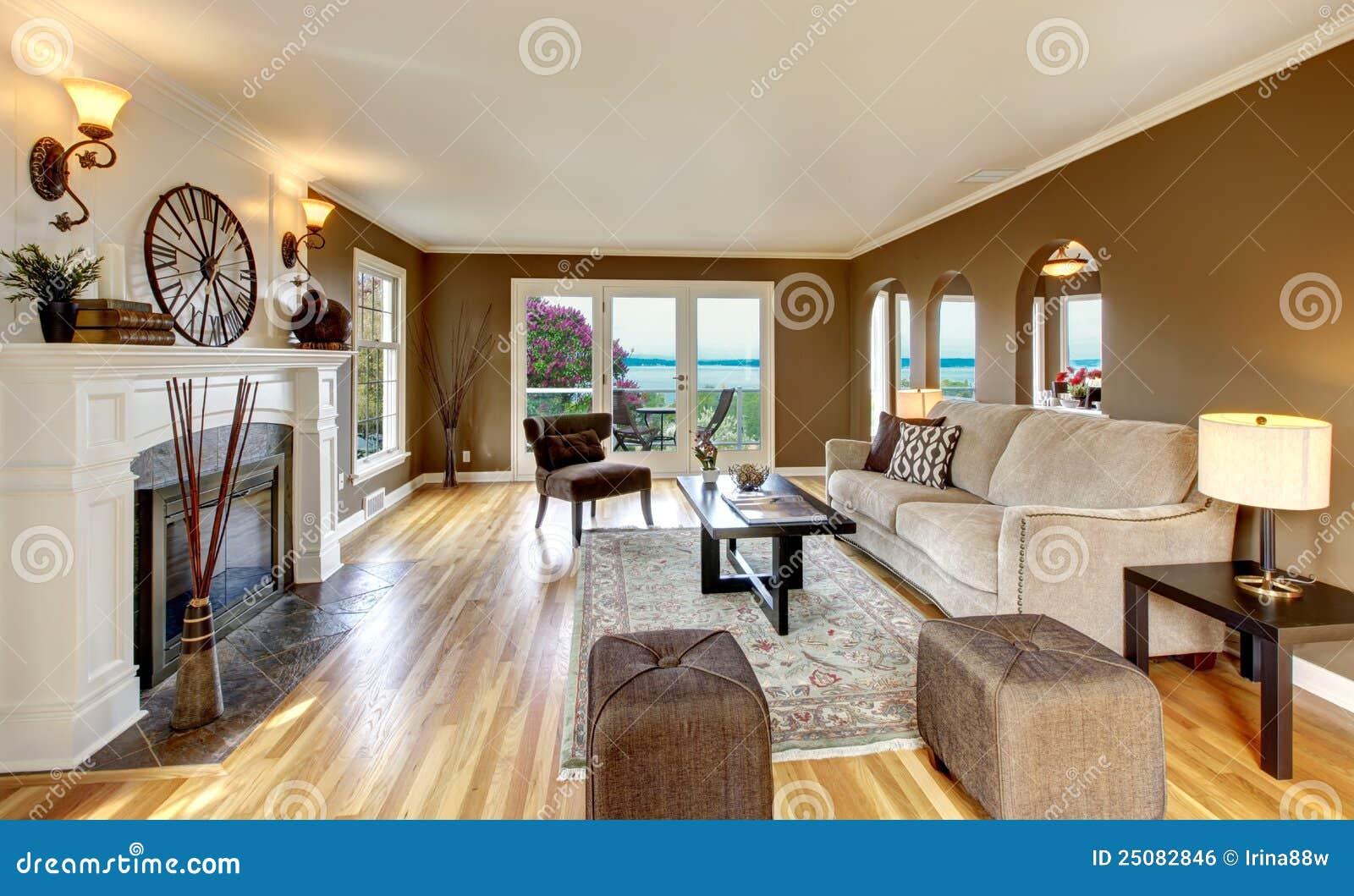 Vardagsrum med ädelträgolvet, spisen och stora fönster. royaltyfri ...