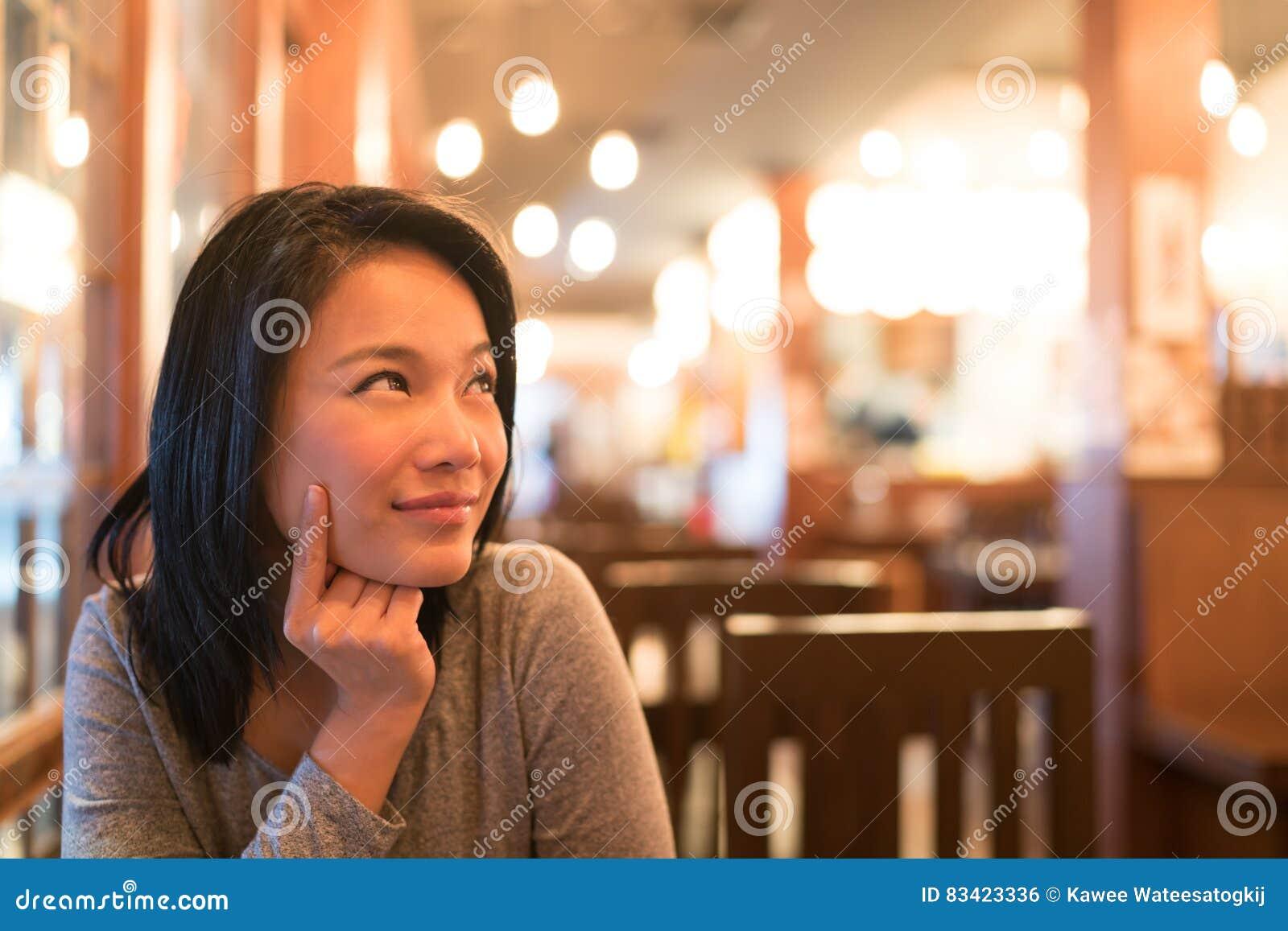 Brunbränd asiatisk flicka som uppåt tänker och ser för att kopiera utrymme som undrar menyn för att beställa för matställe, resta