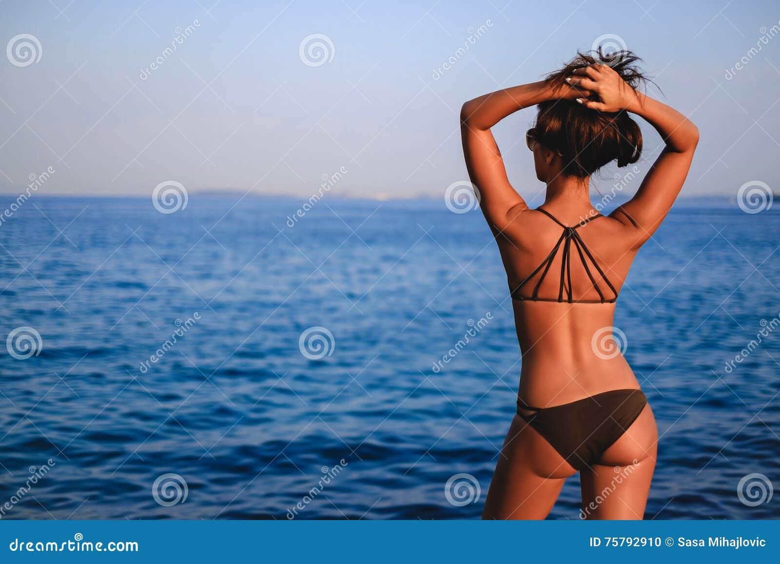 Brunbränd flicka som ser upp horisonten och lyfter hår