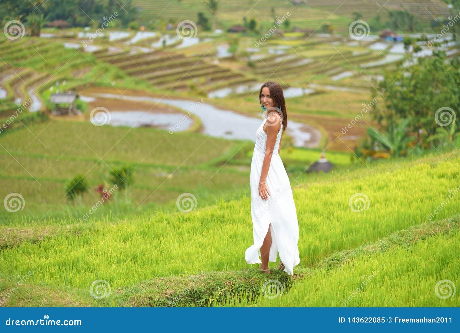 Brunbränd ung kvinna som poserar på bakgrunden av risfält