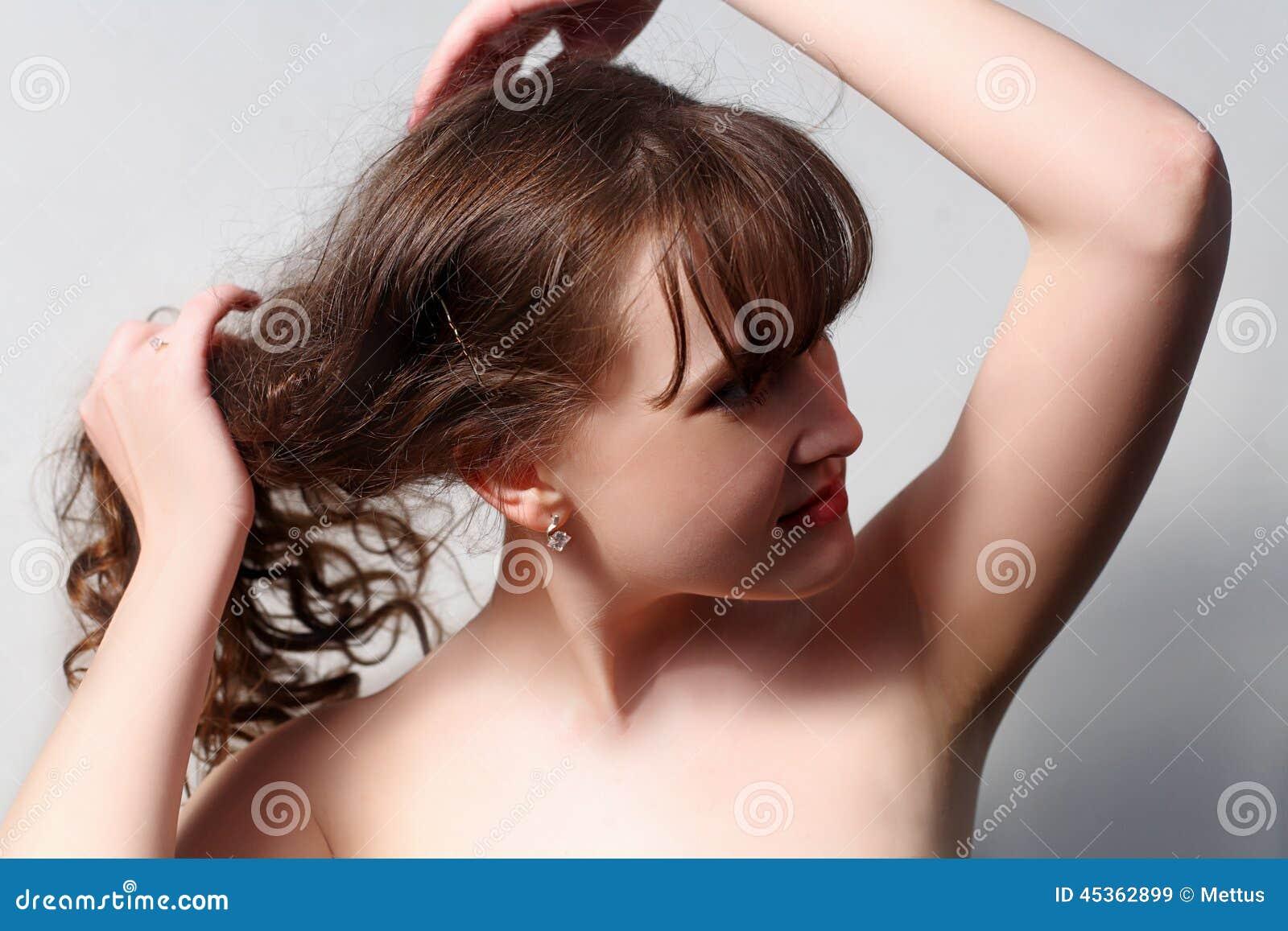 Brune aux cheveux longs sur le gris regardant loin