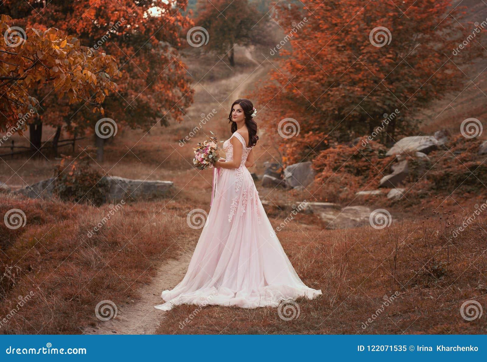 Brune de fille avec de longs cheveux, dans une robe rose luxueuse avec un long train La jeune mariée avec un bouquet pose contre