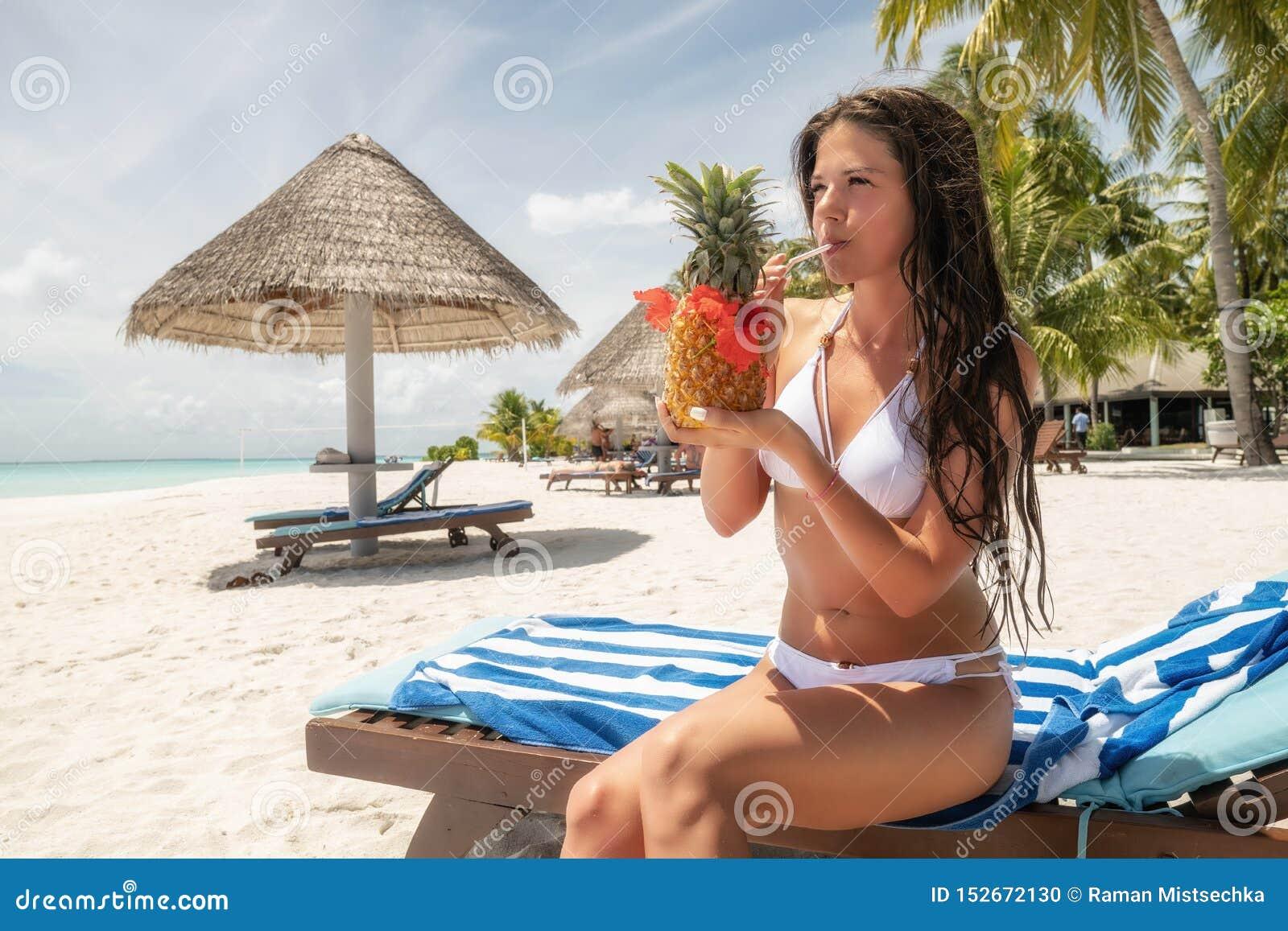 Brunetka w białym kostiumu kąpielowym siedzi na lounger i pije Pina Colada koktajl w ananasie