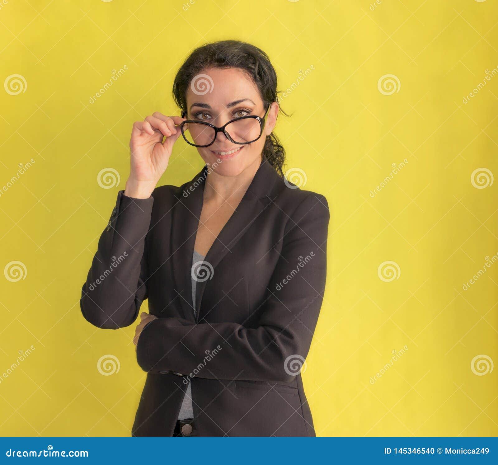 Brunetki biznesowa kobieta zdejmuje jej szkła i ono uśmiecha się przy kamerą