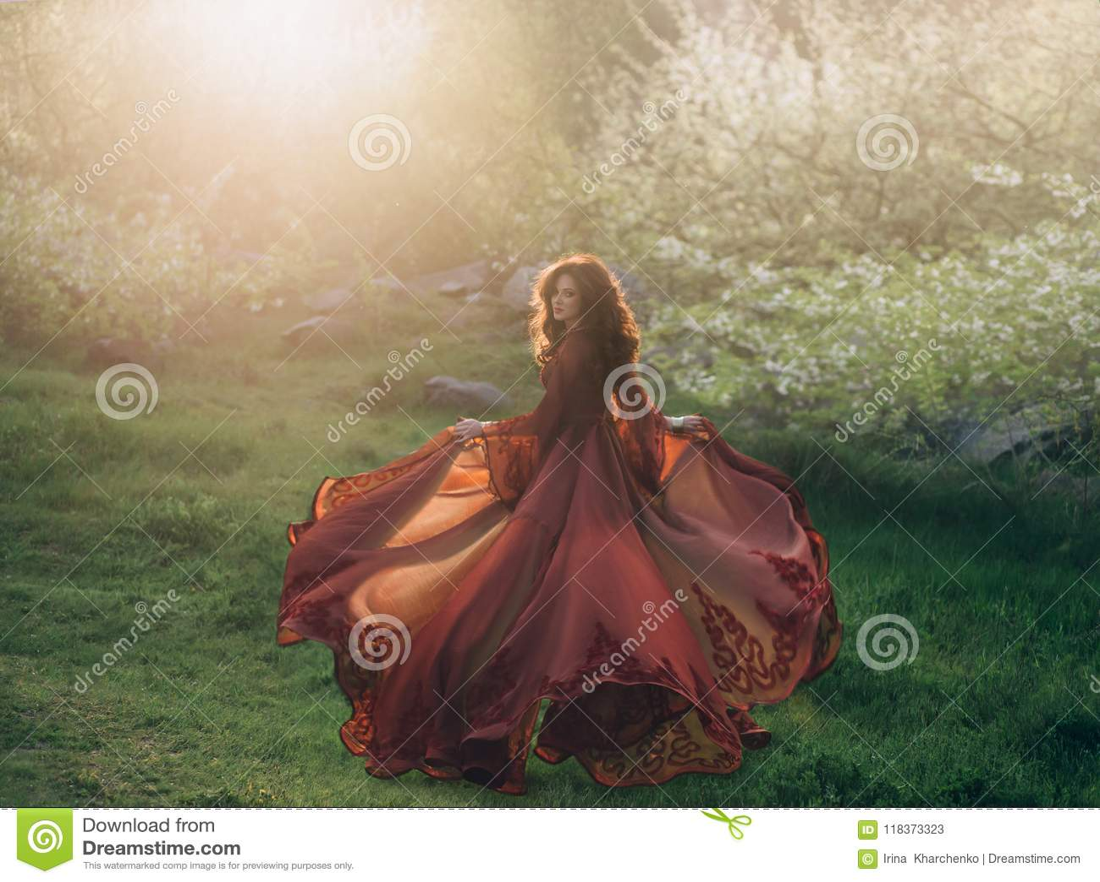 Brunetki dziewczyna z falistym, gęstym włosy, biega spotykać słońce przy zmierzchem Na princess jest luksusowy, czerwieni suknia
