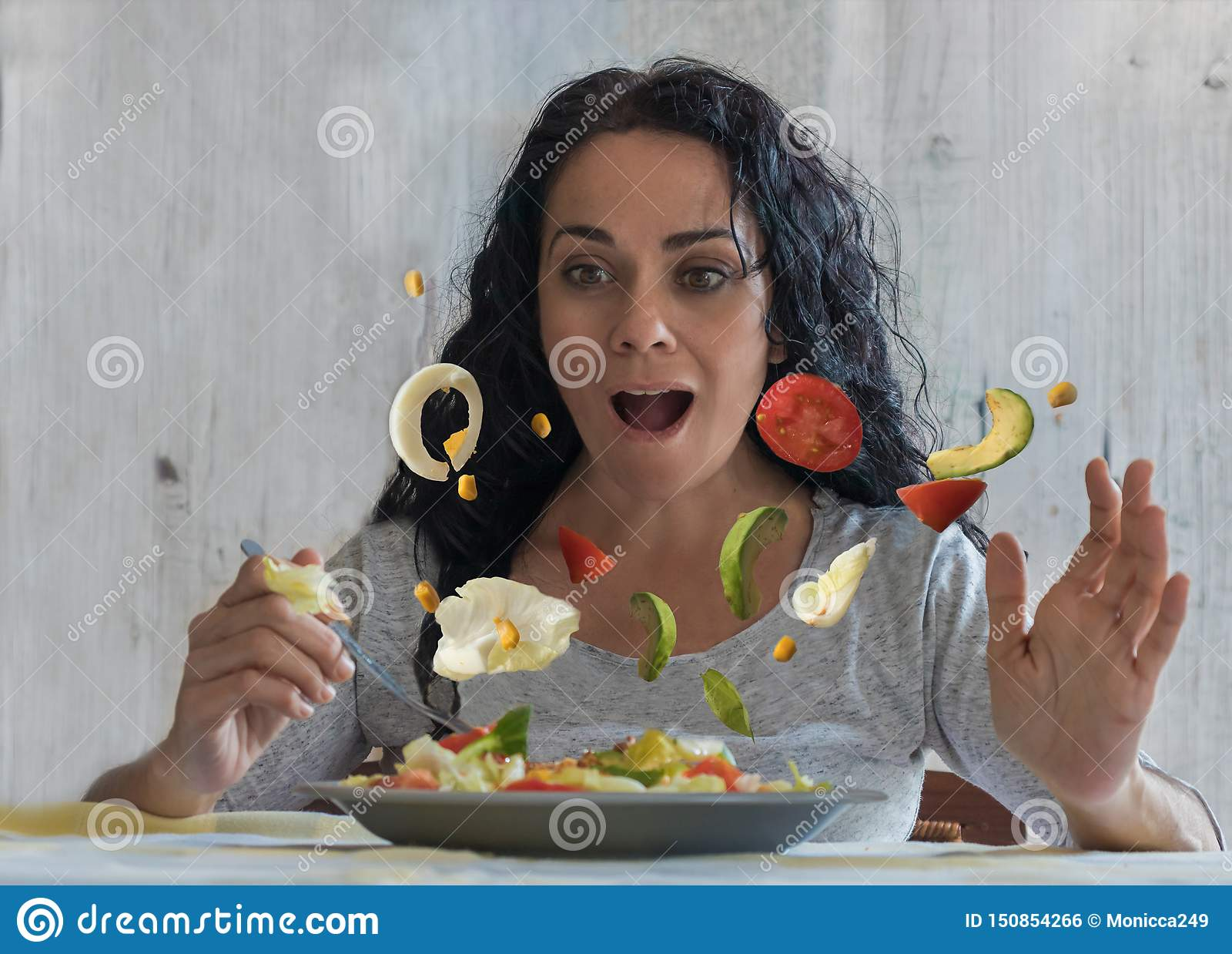 Brunetki kobieta patrzeje zaskakujący jako warzywa w jej sałatkowym początku latać