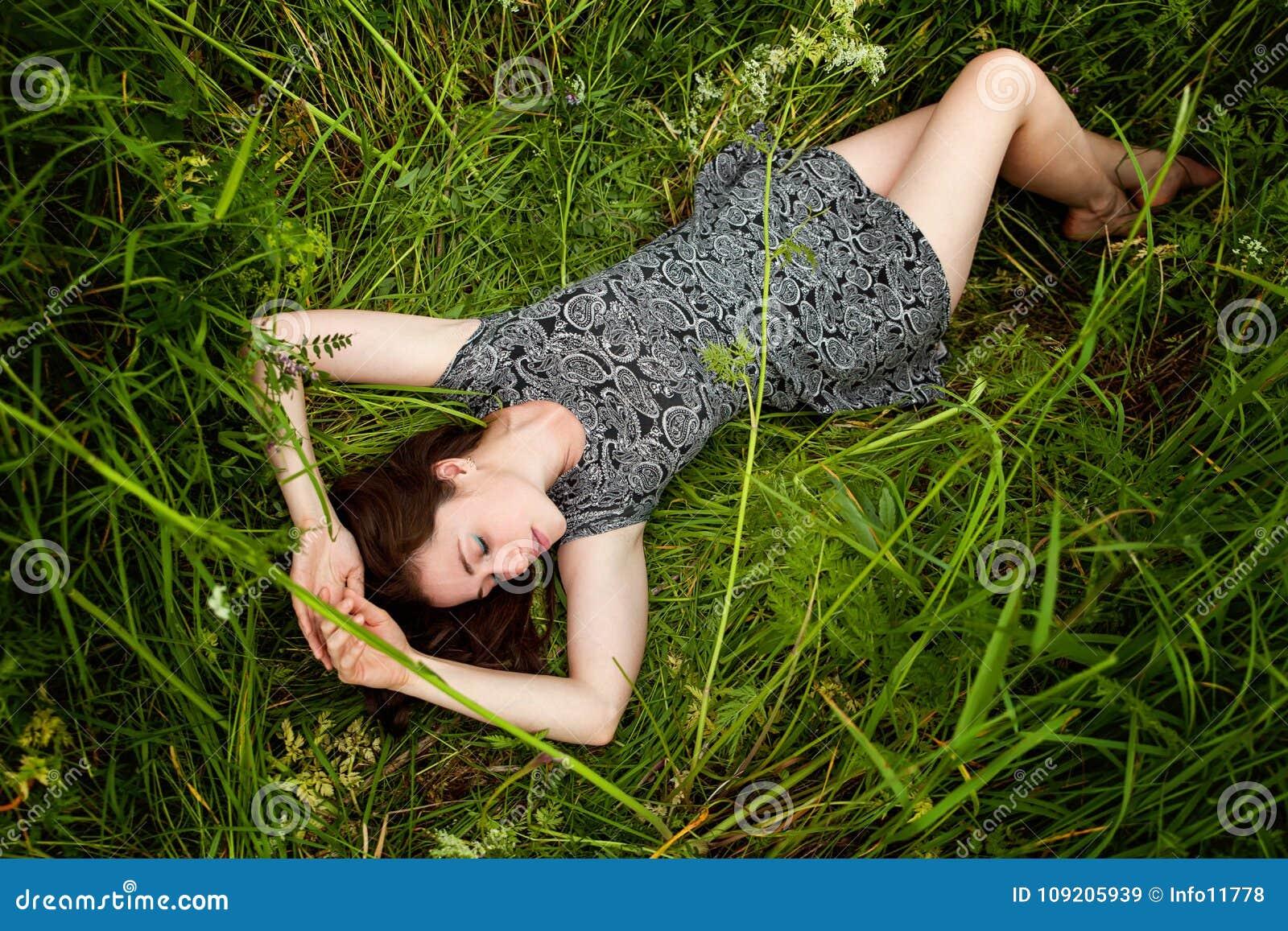 Brunetki kobiety lying on the beach na zielonej trawie