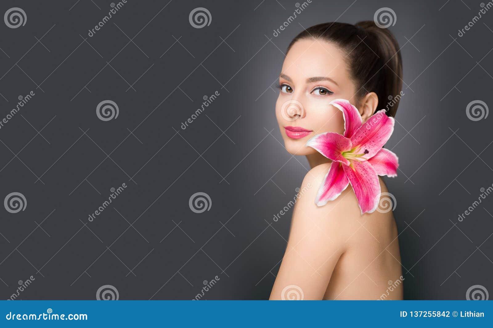 Brunetki piękno z kolorowym kwiatem