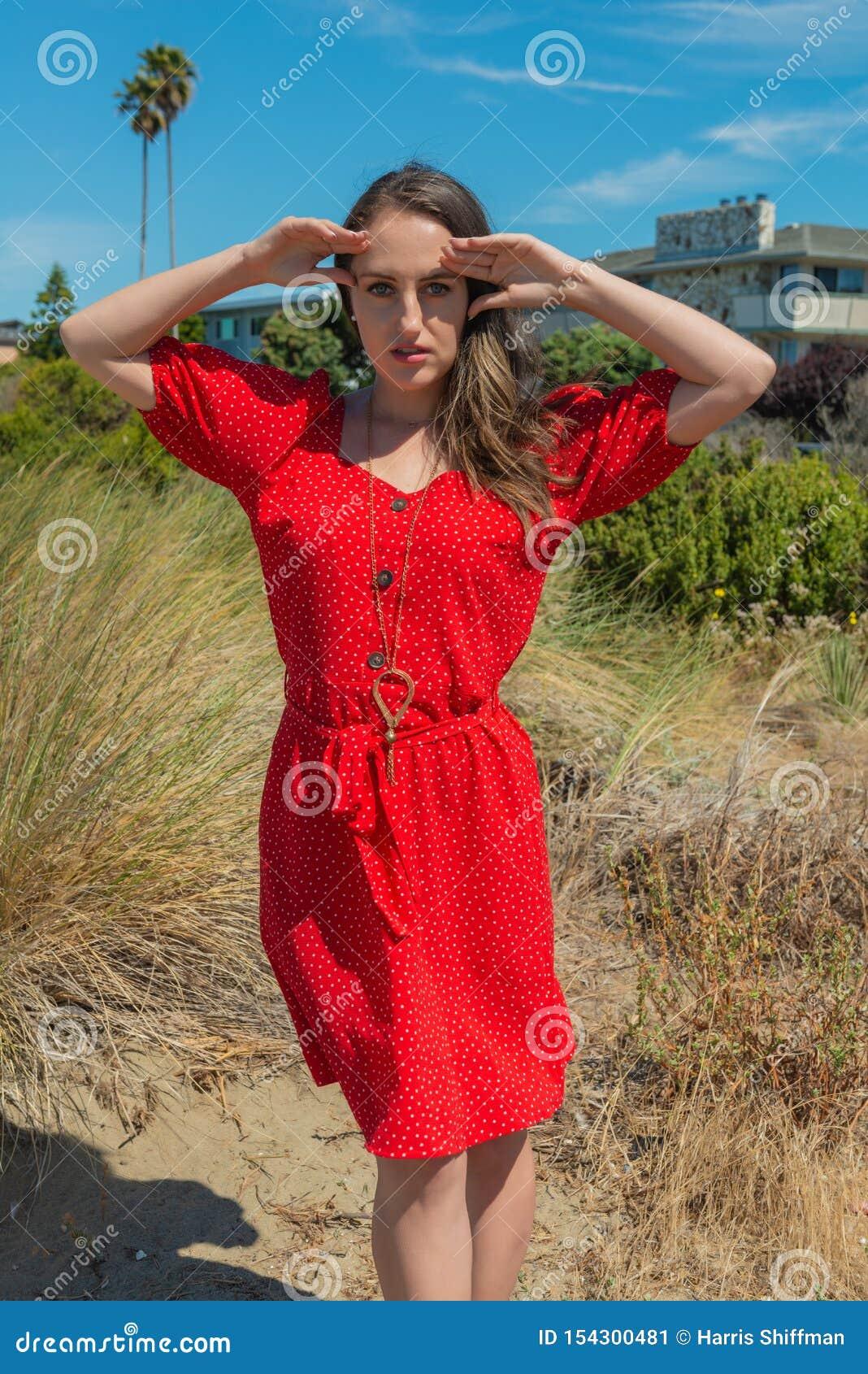 Brunett i rött på en strand