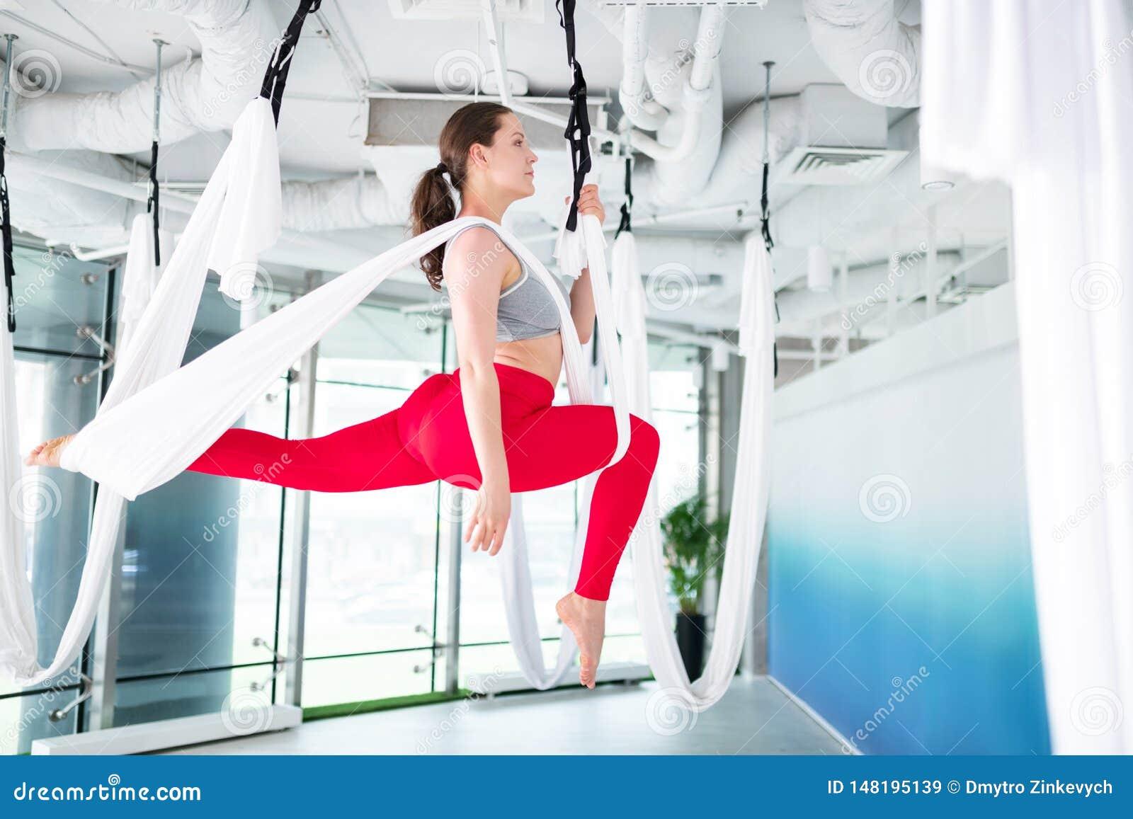 Brunett med hästsvansen som gör flyg- yoga