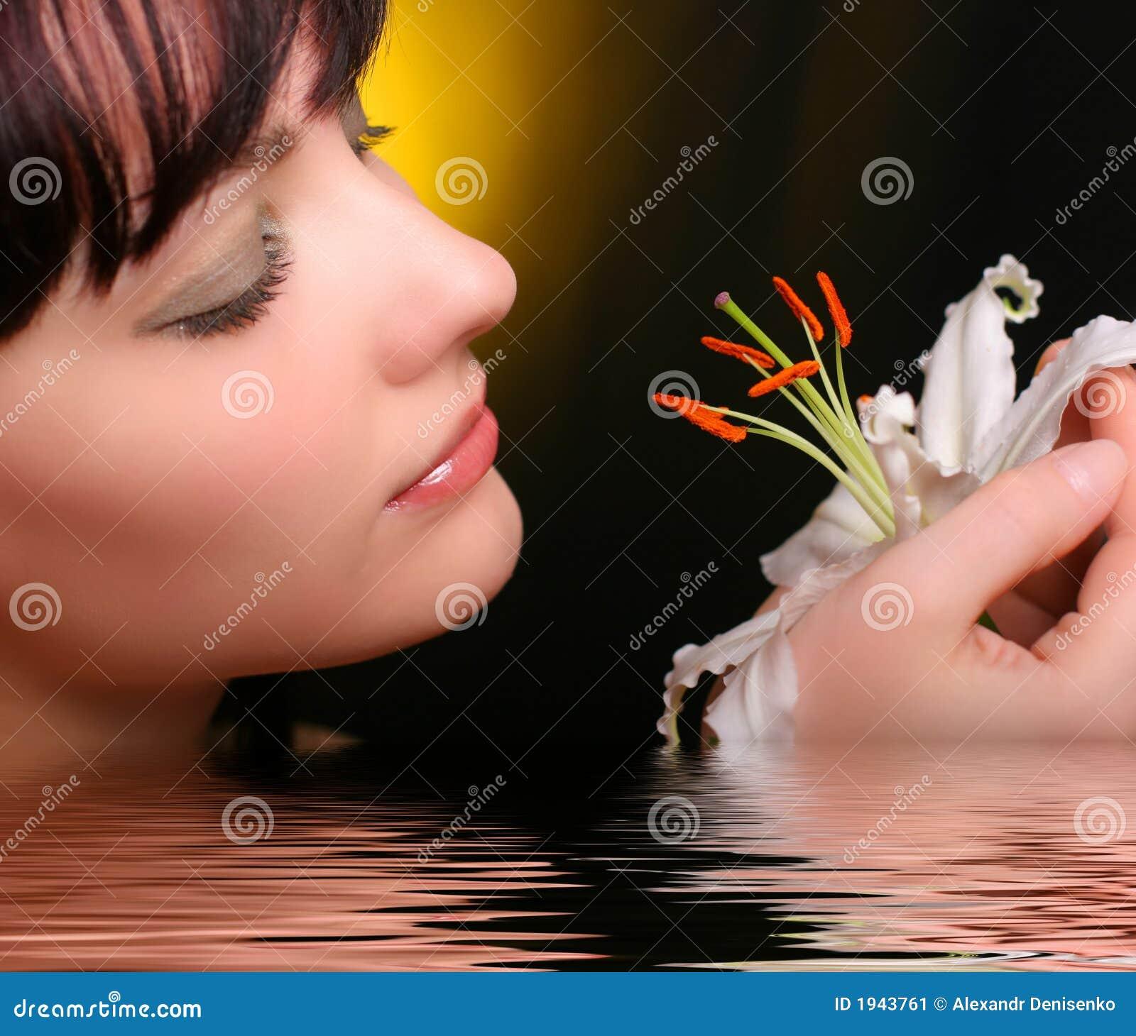 Brunette avec des fleurs de lis blanc dans l eau