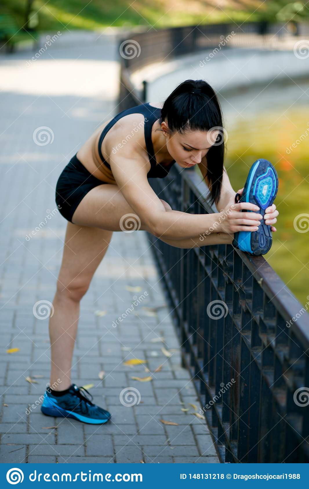 Sporty beautiful young woman practicing stretches exercises on legs, working out, wearing sportswear.