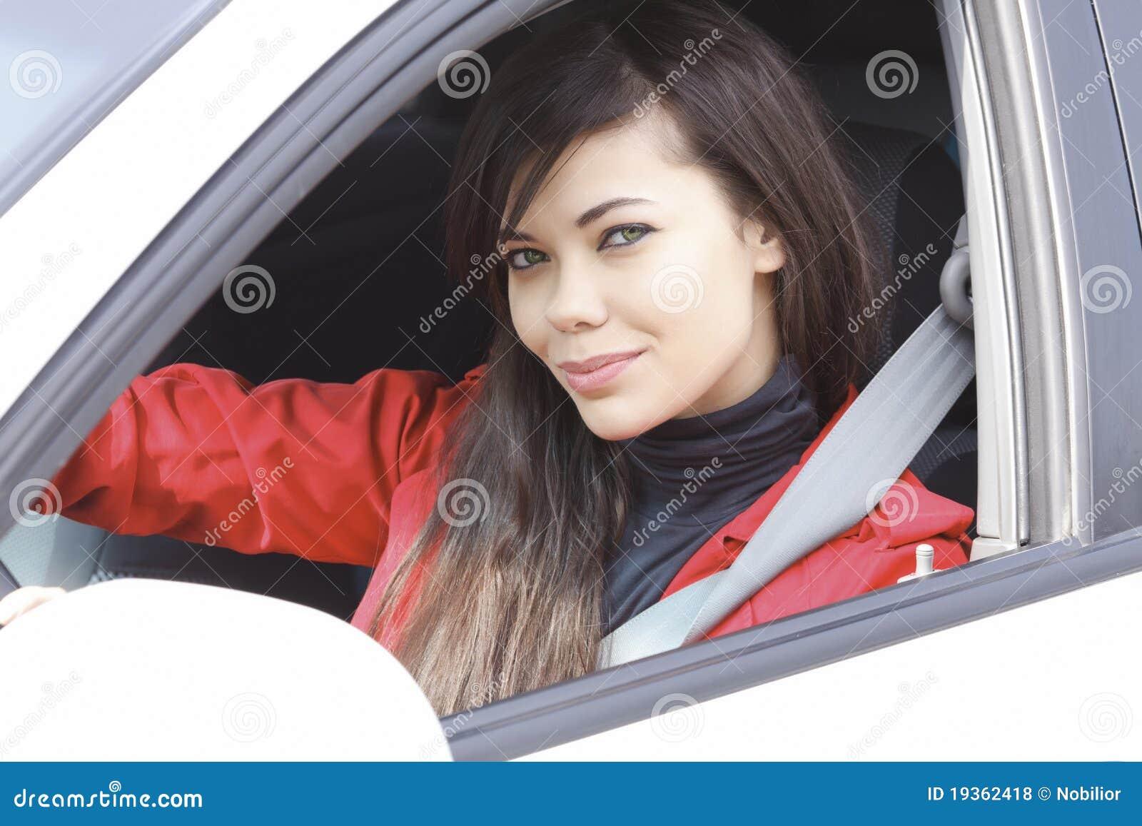 Brunette bonito que conduz um carro