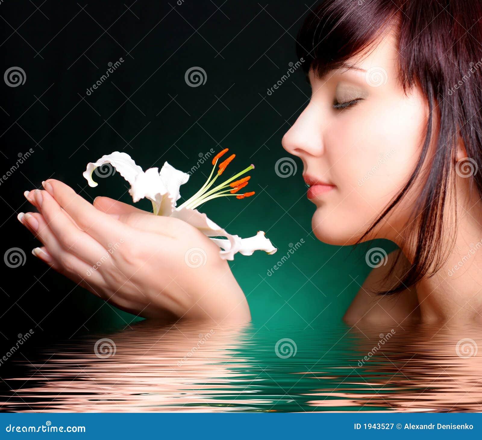 Brunette con i fiori del giglio bianco in acqua