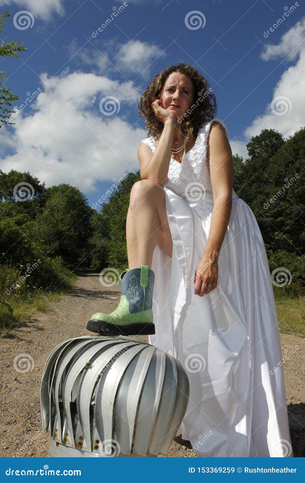 Brunette Cowgirlbraut auf einer Turbine draußen