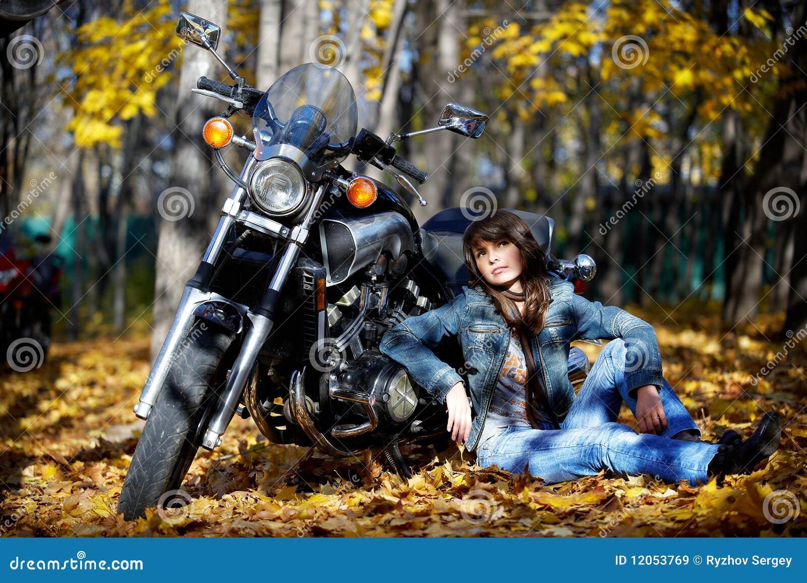 Brunette da menina com uma motocicleta