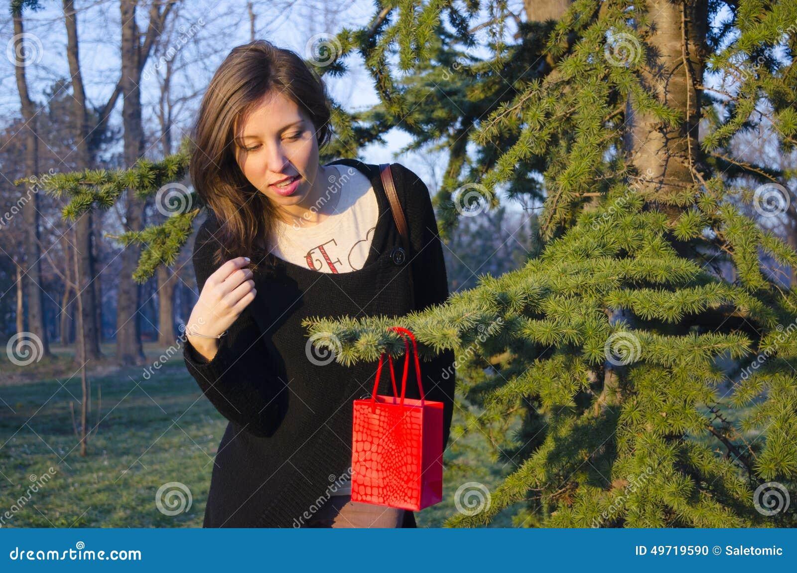 Brunette, der das Geschenk ihres Valentinsgrußes auf einem Baum findet