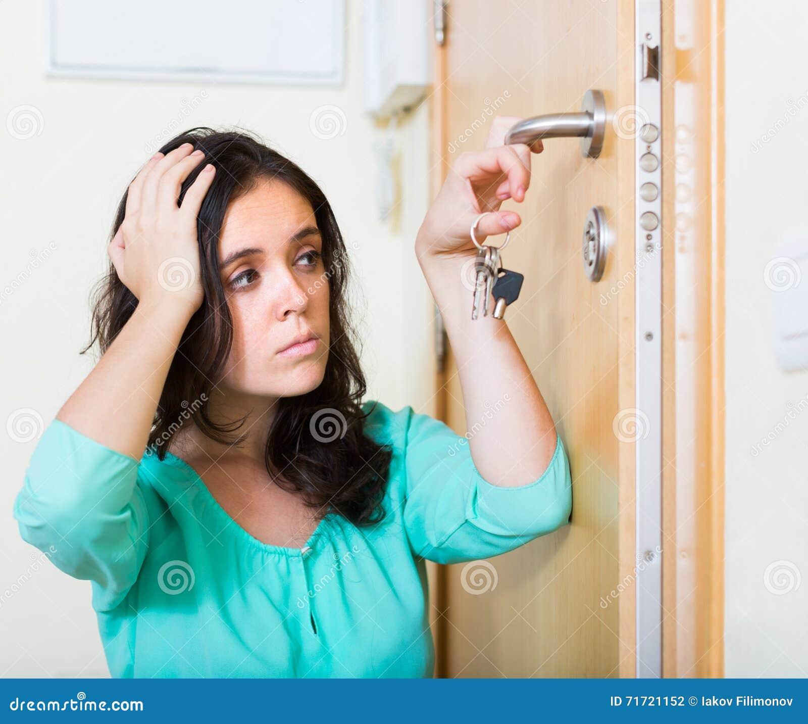 Brunette die gebroken slot van deur bekijken