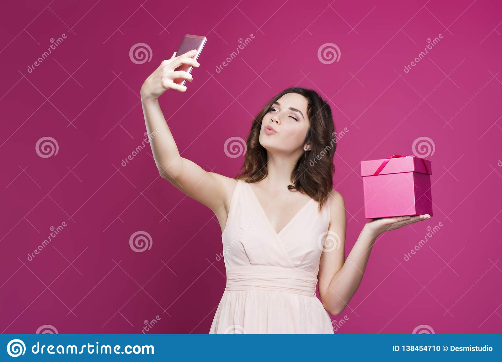 Brunette in a dress makes selfie and holds a gift box