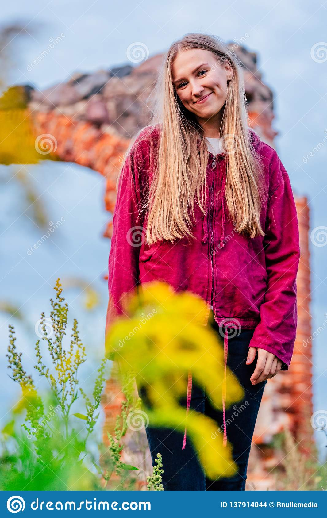 Brunette Female Fashion Model in Countryside Environment with Purple Sweater and Dark Blue Jeans - Sunny Autumn Day