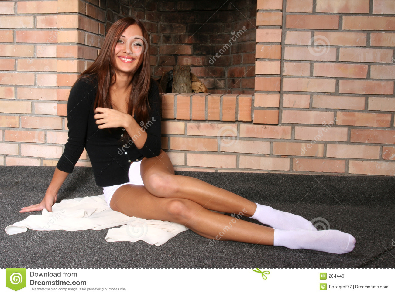 Brunette at a fireplace