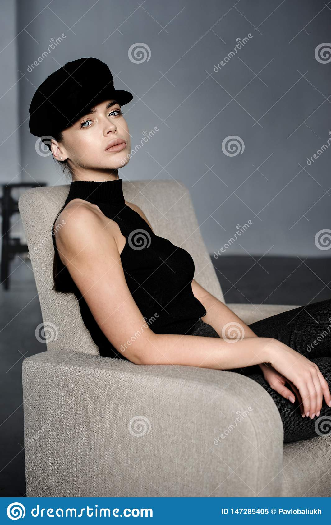 Brunette girl in black with cap posed at studio on chair