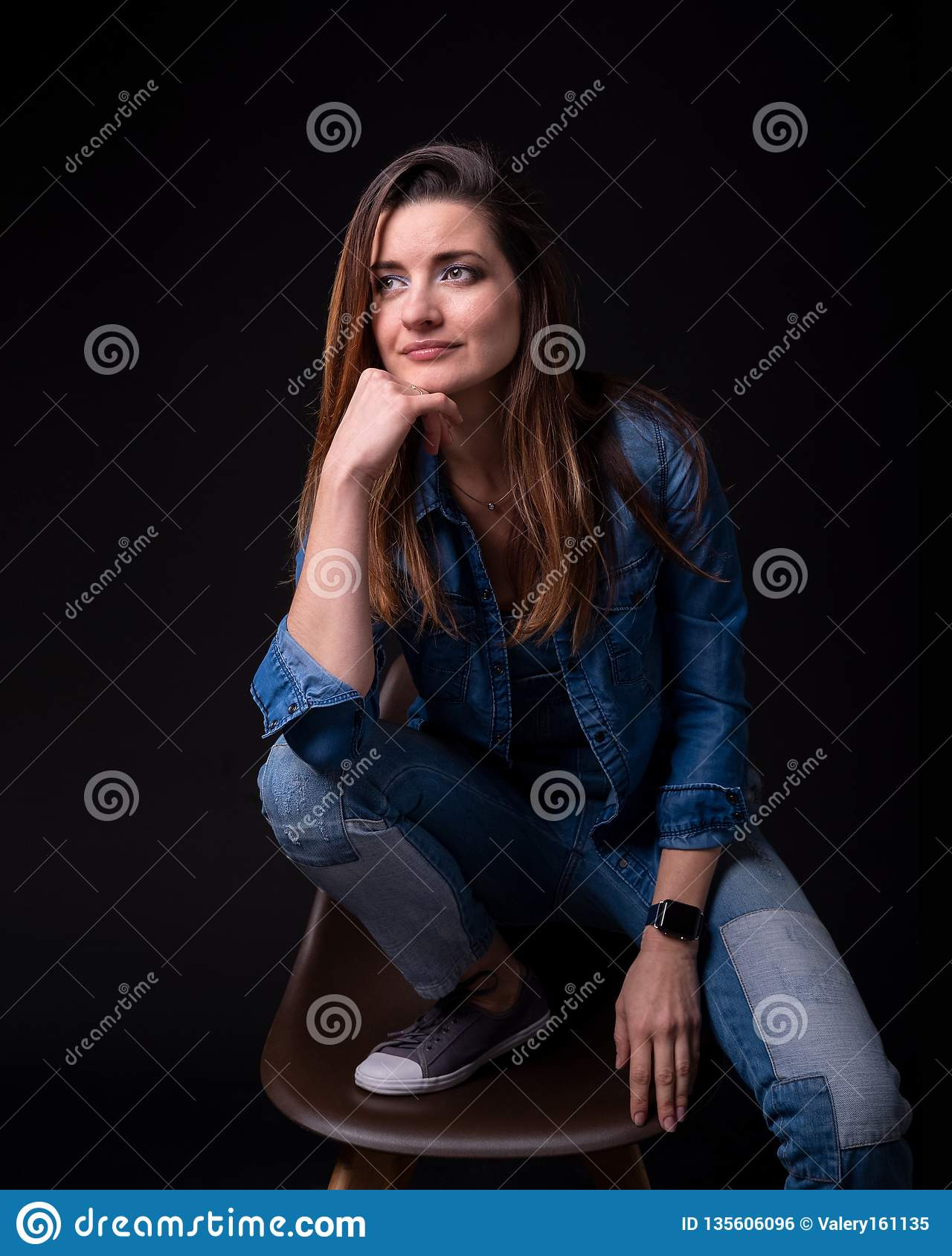 Brunette girl in blue denim jacket and pants