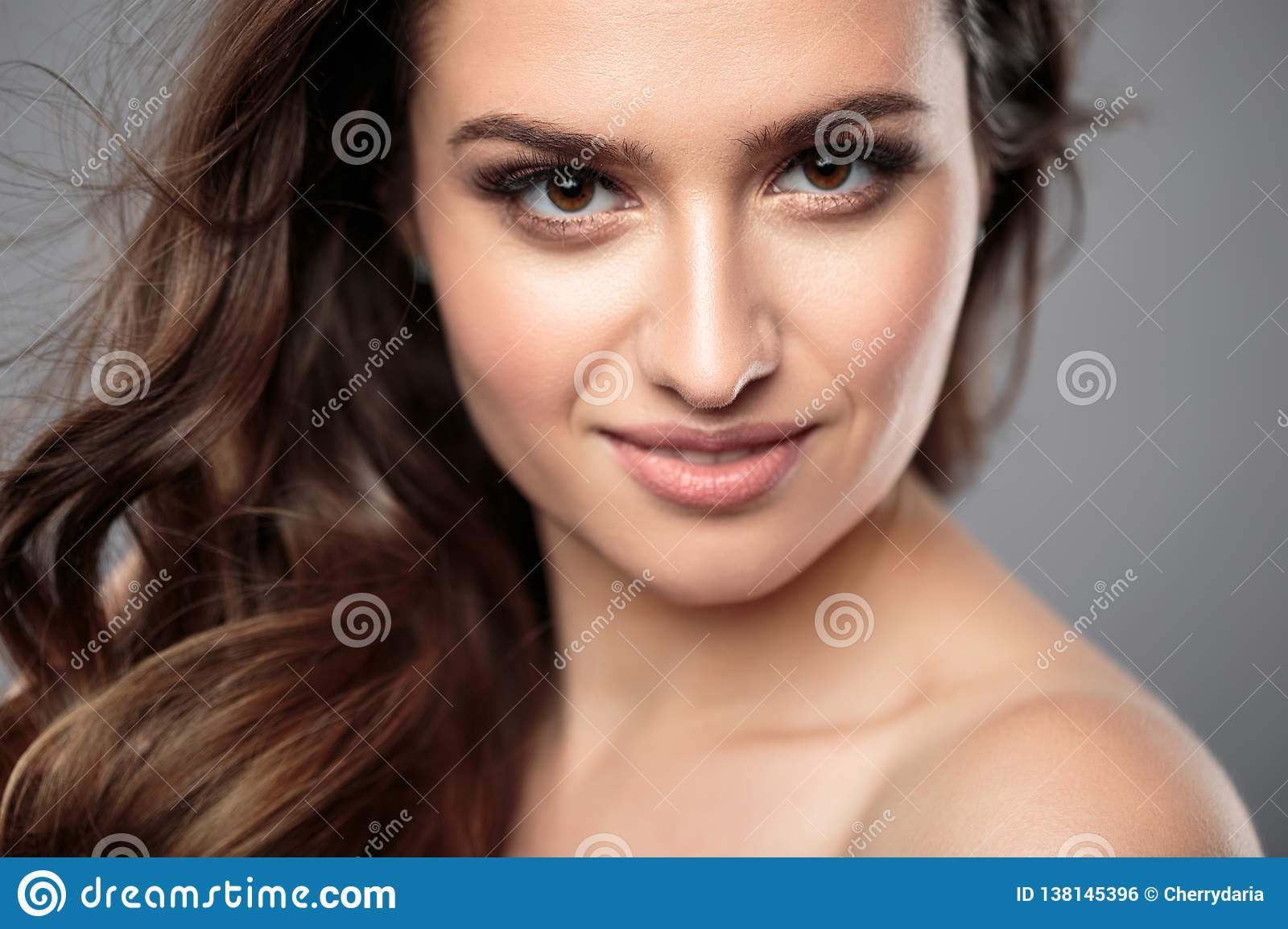 Portrait of beautiful brunette woman with long curly hair