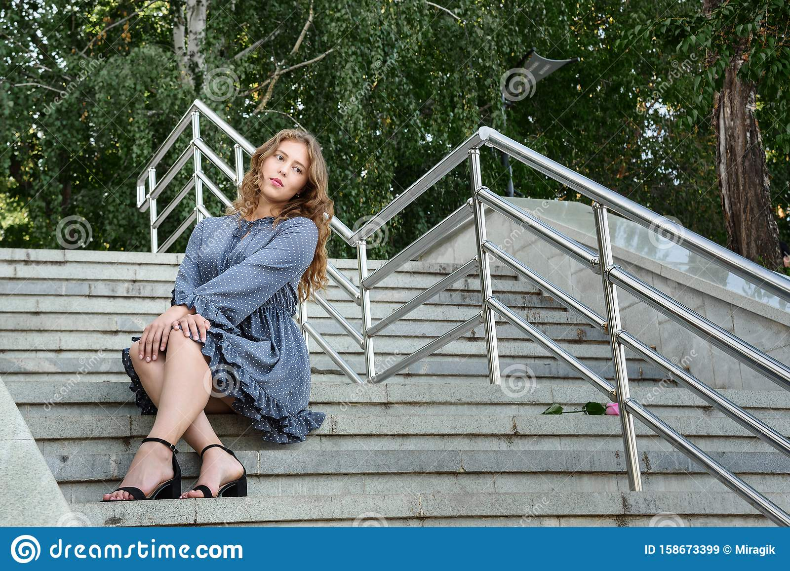 Brunette Girl Sitting On Stairs In The City Girl In Blue