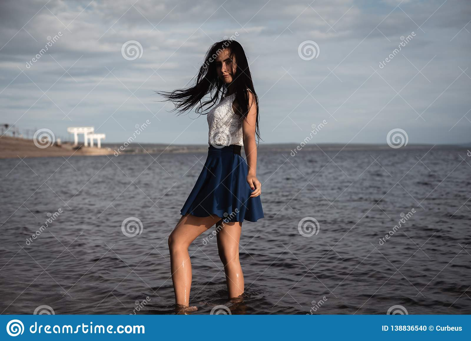 Brunette girl in a skirt standing in the water with her hair down. against the background of concrete and hydroelectric power.