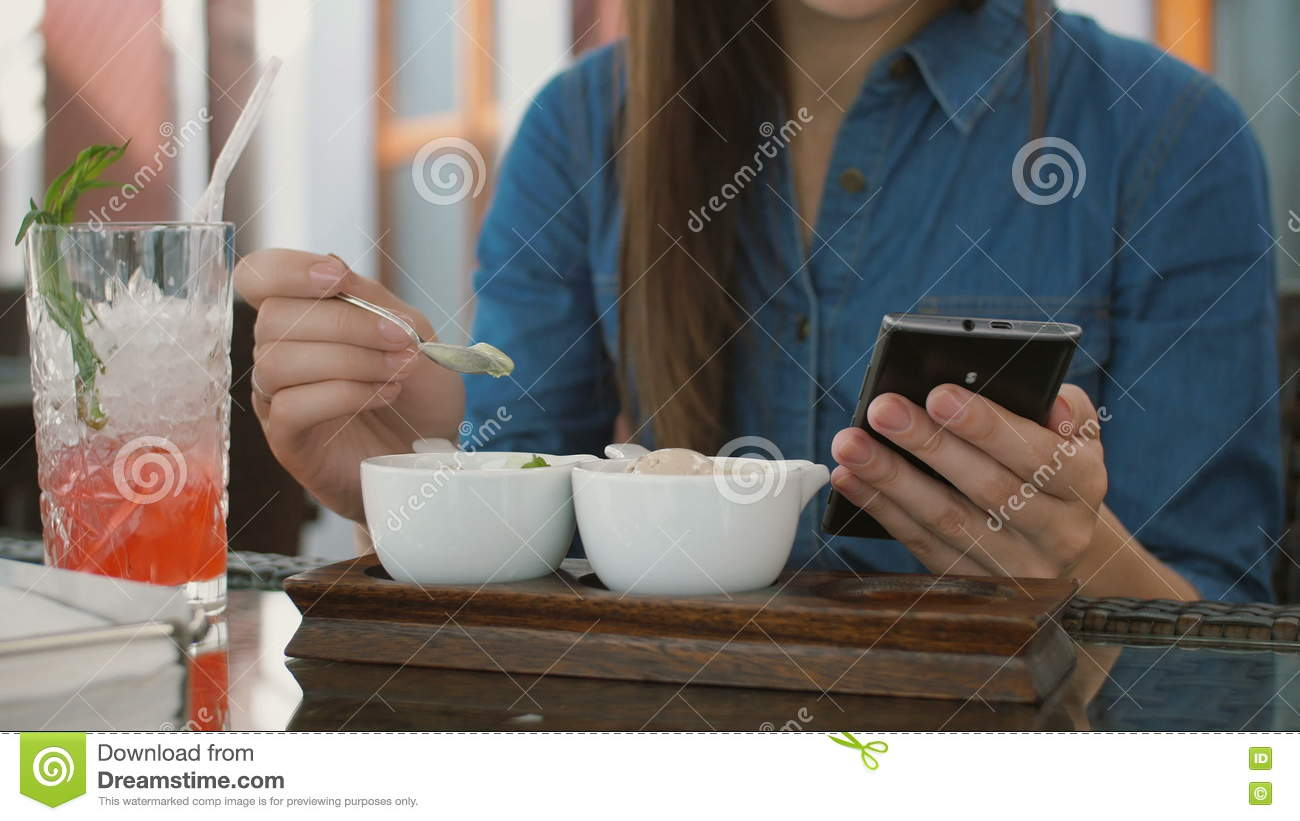 Brunette Girl Uses Smart Phone While Sitting Outside In A Cafe