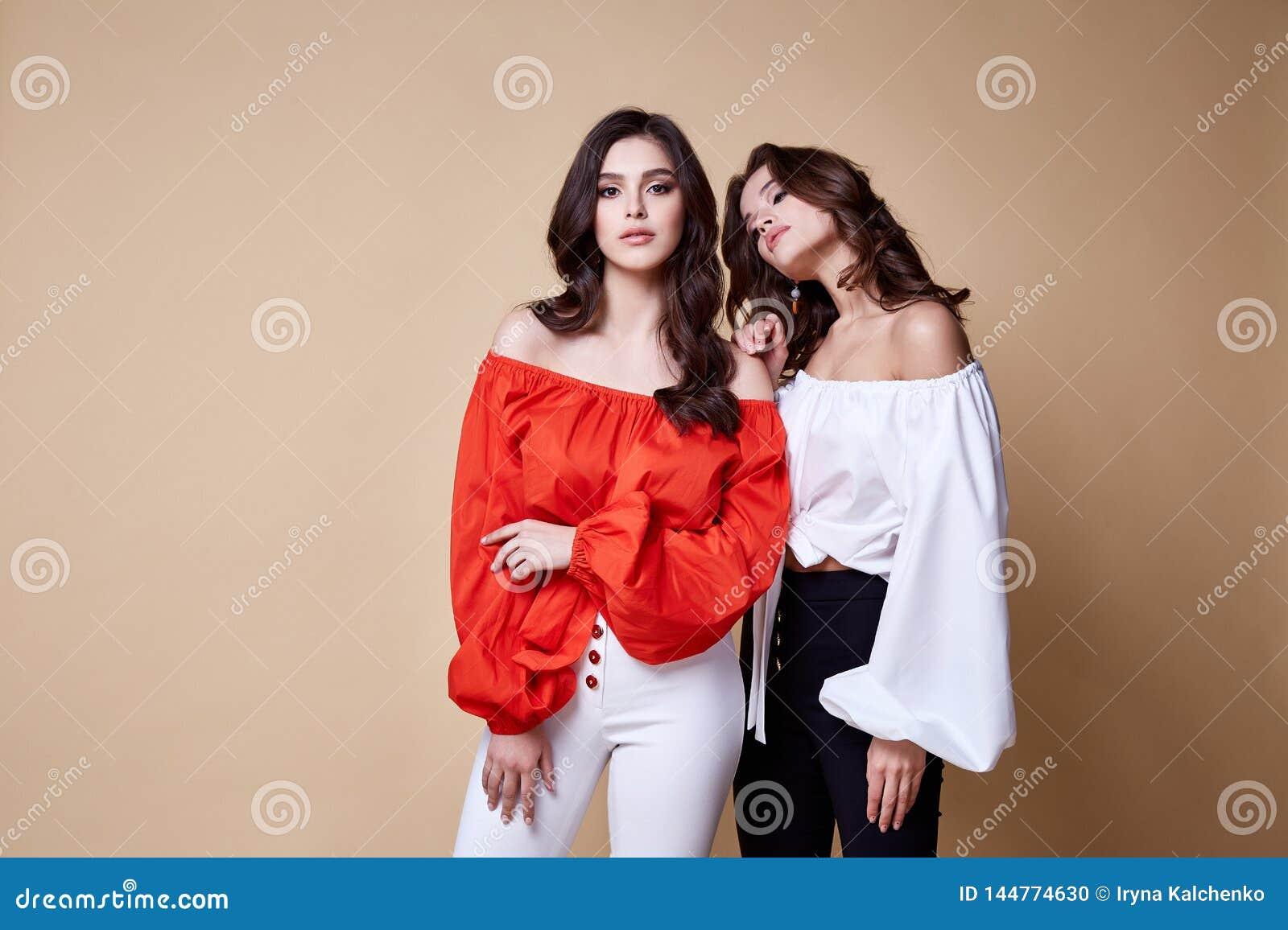 Η προκλητική όμορφη γυναικών μόδας τρίχα brunette γοητείας πρότυπη makeup φορά τα ενδύματα παντελονιού μπλουζών μεταξιού για το κ