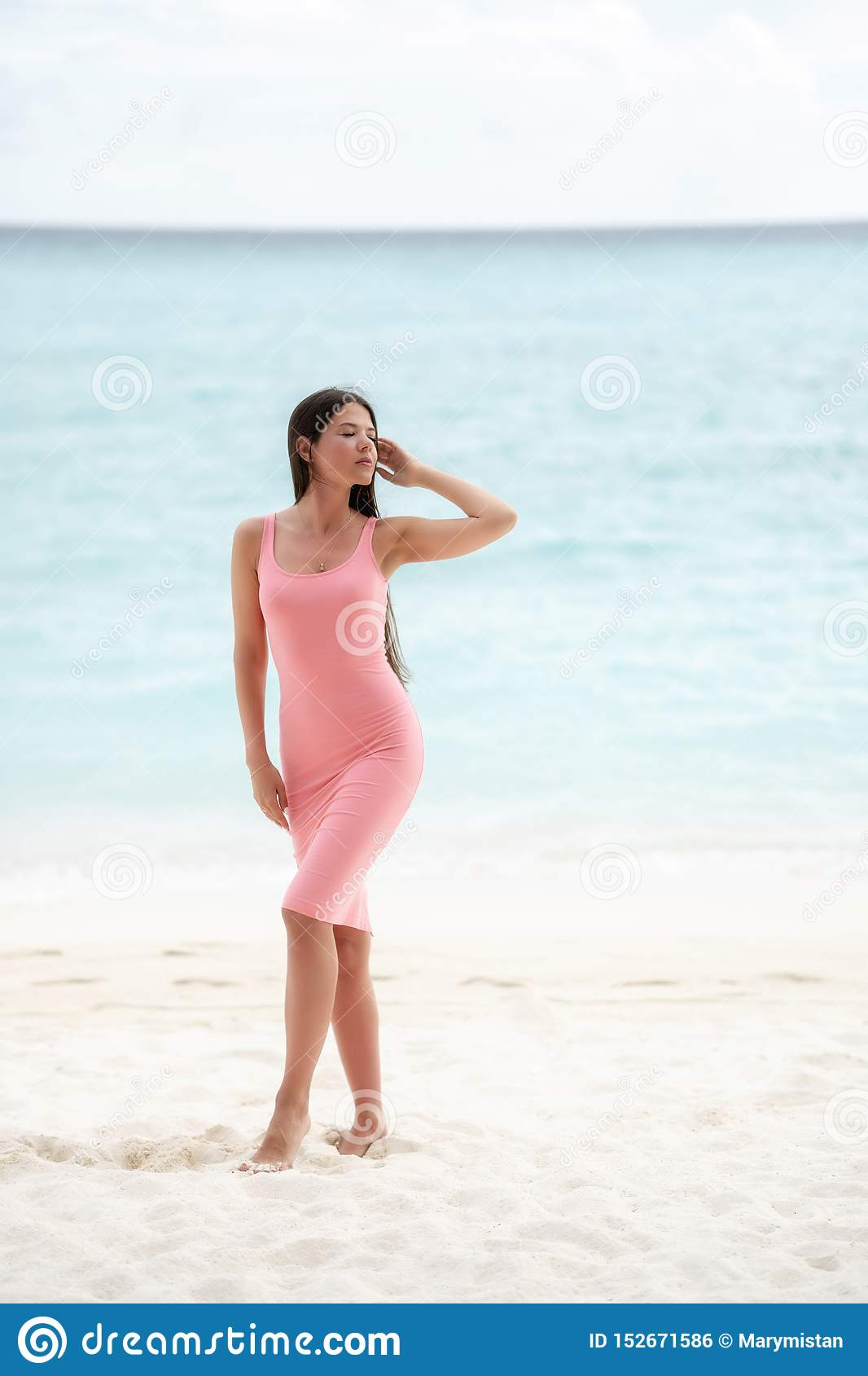 The brunette in a pink fitting dress walks on a snow-white beach