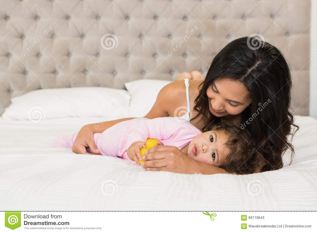 Brunette playing with her baby and a duck