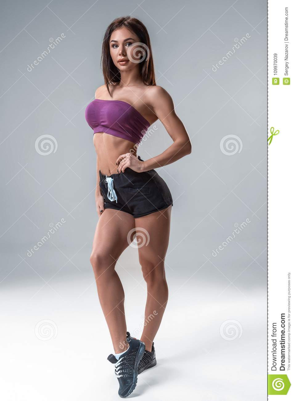 6fd6ab2fe Brunette fitness girl in sport wear with perfect body in the studio posing  before training set. A woman is dressed in short shorts in a purple top.